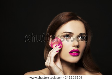 Fashion, health, beauty and spa concept - beautiful woman with rose leaf sponge and pink lips, pink manicure, in black background  - stock photo