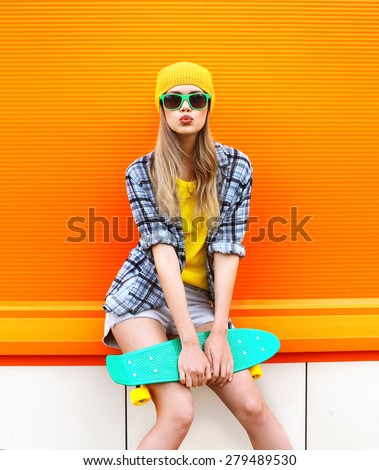 Fashion hipster cool girl in sunglasses and colorful clothes with skateboard having fun against the orange wall - stock photo