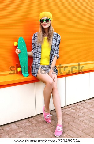 Fashion hipster cool girl in sunglasses and colorful clothes with skateboard having fun outdoors against the orange wall - stock photo