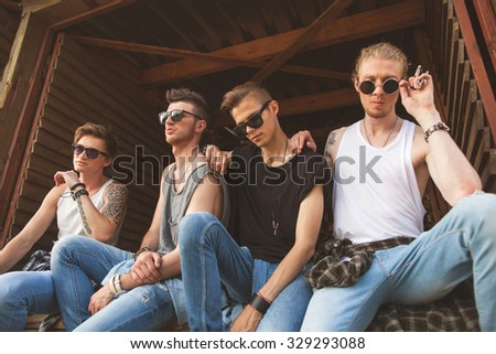 fashion hipster guys sitting near the wooden wall, dressed in jeans and a plaid shirt, sunglasses, Vogue Style