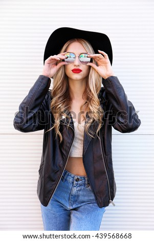 Fashion hipster woman posing outdoor. Black hat, leather jacket, blond curly hair, bright red lips, sunglasses.Trendy fashion style - stock photo