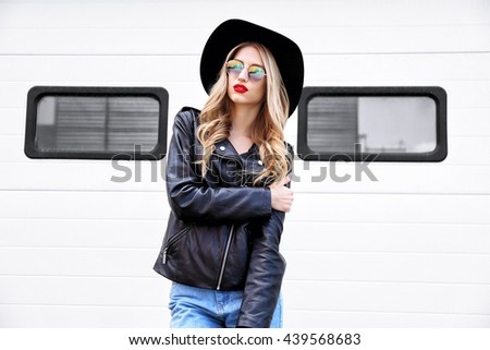 Fashion hipster woman posing outdoor. Black hat, leather jacket, blond curly hair, bright red lips, sunglasses.Trendy fashion style