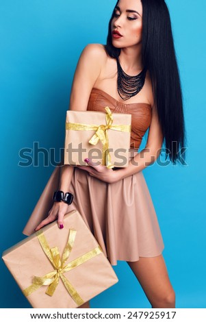 fashion holiday photo of sexy brunette woman with long hair, bright make up in short leather top and skirt with accessories lying in a boxes with gifts and holding a presents at studio
