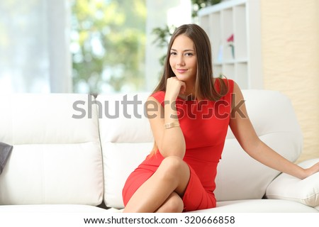Fashion housewife woman in red posing on a couch at home and looking at camera - stock photo