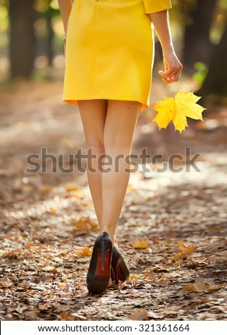 Fashion image of perfect long slim woman legs on autumn road. - stock photo