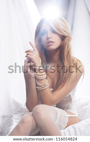 Fashion image of young and sexy redhead woman in white lingerie - stock photo