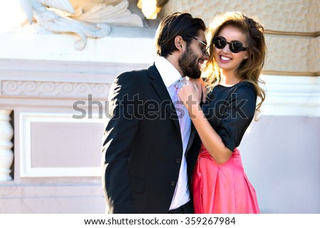 Fashion image of young blonde woman posing with her boyfriend on the street, old european city center, luxury glamour clothes, elegant couple in love, happy time, vacation, joy. - stock photo