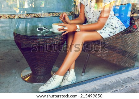 Fashion image taken through the window of cafeteria, young woman with perfect legs, sitting alone and drinking coffee,and whiting for her boyfriend, vintage playfull outfit. - stock photo