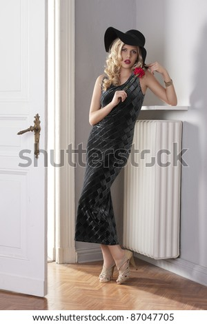 fashion indoor shot of a beautiful blond curly haired girl with long elegant black dress and a black hat near old fashioned door with red flower in hand - stock photo