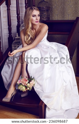 fashion interior photo of beautiful bride with blond hair in elegant wedding dress,holding a bouquet of flowers,sitting on stairs