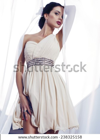fashion interior photo of beautiful sensual woman with dark hair wearing elegant cocktail dress - stock photo