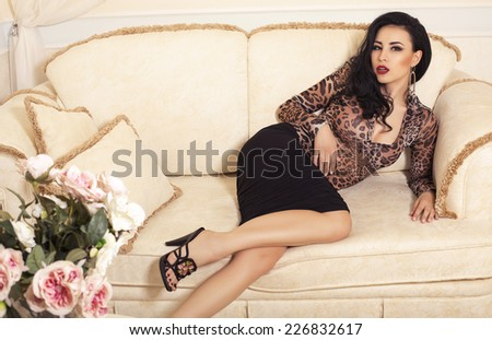 fashion interior photo of beautiful sensual woman with dark hair wearing elegant dress and shoes lying on divan in bedroom