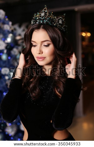 fashion interior photo of beautiful sensual woman with long dark hair wears elegant dress and precious crown, posing beside decorated Christmas tree