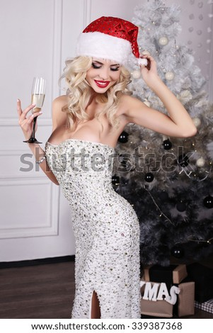 fashion interior photo of beautiful sexy girl with blond hair wears luxurious dress and red Santa hat,holding glass of champagne in hand,posing near Christmas tree