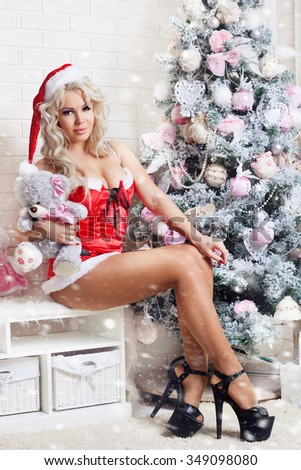 fashion interior photo of beautiful sexy girl with blond hair wears luxurious dress,holding glass of champagne in hand,posing near Christmas tree - stock photo