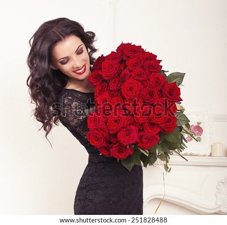 fashion interior photo of beautiful smiling woman with dark hair in elegant lace dress, holding a big bouquet of red roses in Valentine's day - stock photo