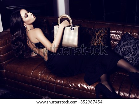 fashion interior photo of beautiful woman with dark curly hair and evening makeup,wears elegant dress, holding bag in hands  - stock photo