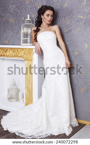 fashion interior photo of beautiful young bride with dark hair in elegant wedding dress posing in luxurious studio