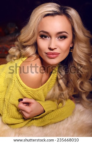 fashion interior photo of sexy beautiful woman with blond hair wearing yellow sweater relaxing beside a chimney at bedroom  - stock photo