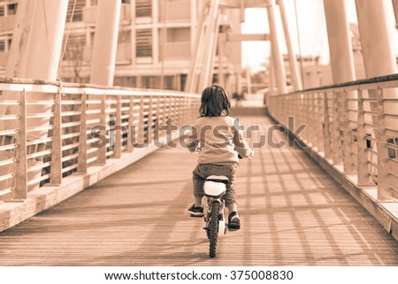 Fashion italian child driving bicycle on the bridge - Little boy on bike in urban contest - Trend and vintage retro concept - Black and white editing - Warm soft brown filtered look - stock photo