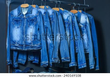 fashion jeans jacket on hangers  - stock photo