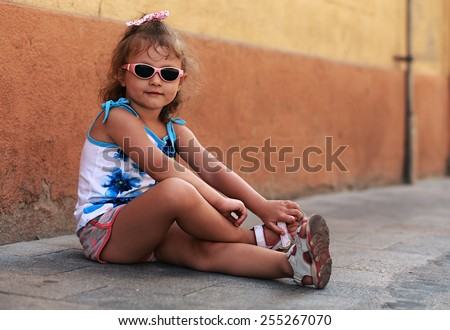 Fashion kid girl in sun glasses sitting on road near the wall and smiling - stock photo
