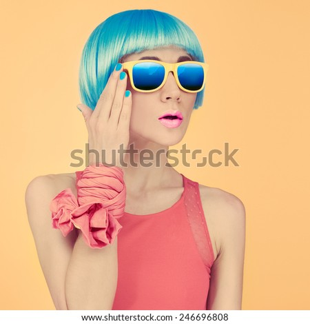 Fashion Lady Surprise in a blue wig and Sunglasses on bright yellow background - stock photo