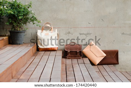 Fashion Leather Bags on grunge concrete background - stock photo