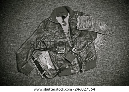 Fashion: Leather jacket, jeans with a belt, shirt, watches, note 5 euros. Retro style, black-and-white photo