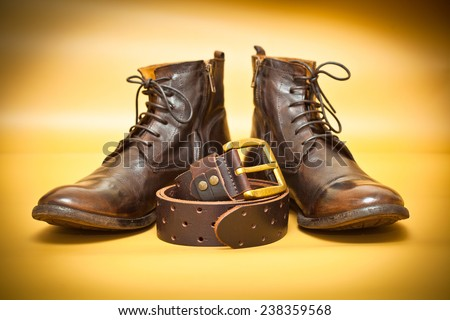 Fashion leather shoes, leather belt with gold buckle. Yellow abstract background