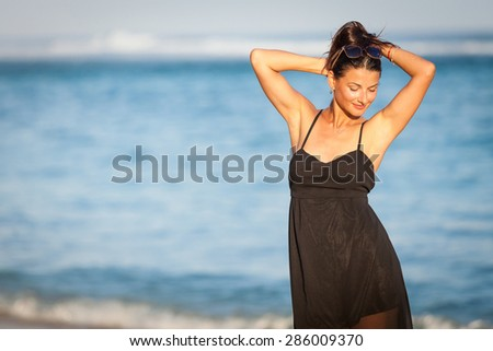 Fashion Lifestyle, Beautiful brunette girl in the sunglasses and black dress on the beach at the day time. Travel and Vacation. - stock photo