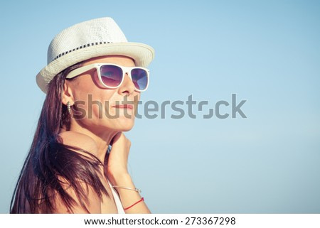 Fashion Lifestyle, Beautiful brunette girl in the sunglasses and white hat on the beach at the day time. Travel and Vacation. - stock photo