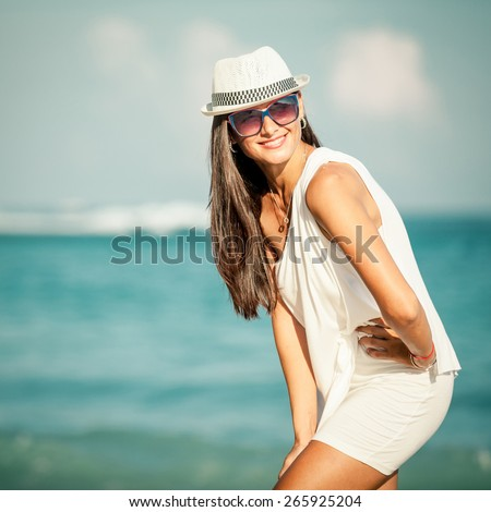 Fashion Lifestyle, Beautiful girl in the sunglasses and white hat on the beach at the day time. Travel and Vacation.