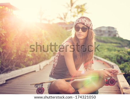 Fashion lifestyle, Beautiful young woman with skateboard, backlit at sunset - stock photo