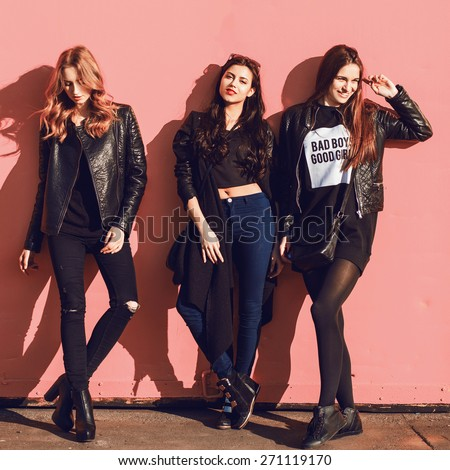 Fashion lifestyle  photo of three  stylish hipster friends in black spring outfit posing against pink urban  wall. - stock photo