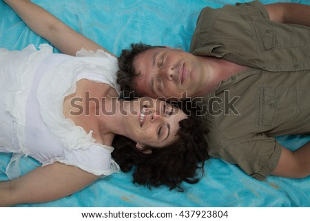 Fashion lifestyle portrait of happy couple lay and relaxed on their vacation, bright sunny summer colors. - stock photo