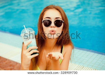 Fashion lifestyle portrait of young happy pretty woman laughing and having fun at pool party and drinking cocktail,listening favorite music at earphones,stylish vintage outfit,bright fresh colors - stock photo