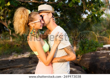 Fashion lifestyle portrait of young perfect  beautiful couple relaxed on their vacation, wearing sunglasses and vintage clothes, bright sunny summer colors.Kissing and  having fun  together.Huggings. - stock photo