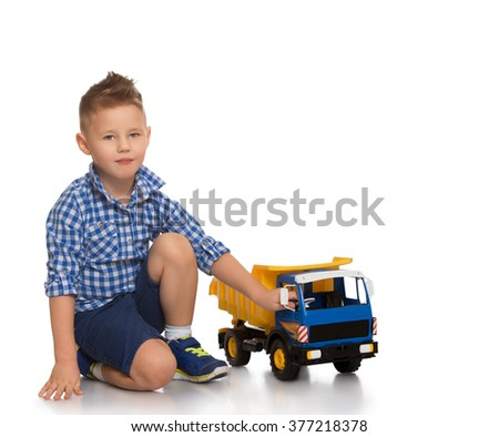Fashion little boy in blue plaid shirt and shorts is sitting on the couch - Isolated on white background
