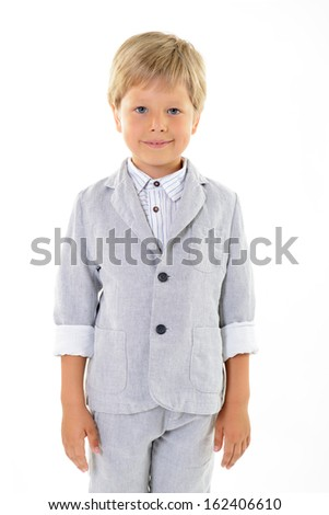 fashion little boy in gray suit posing at studio over white