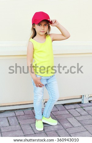 Fashion little girl child wearing a baseball red cap in city - stock photo