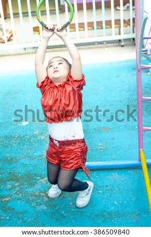 fashion little girl in dancing suit have a fun outdoor. and play the playground.
