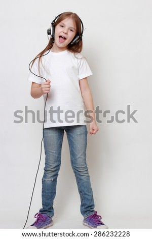 Fashion little girl with headphone singing - stock photo