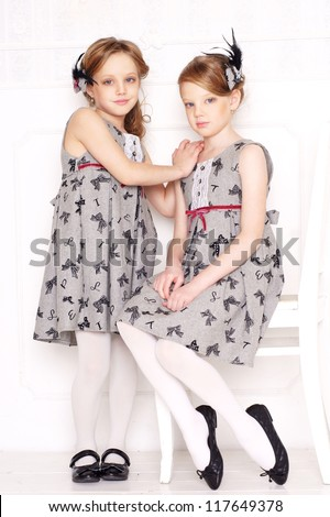 fashion little girls posing in gray dresses