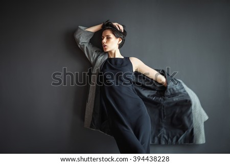 fashion lonely girl in motion posing on dark background - stock photo