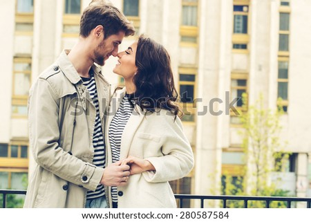Fashion lovely couple posing in the old part of town. Young man and sensual brunette outdoor portrait in stripes  dress. Outdoors, lifestyle. - stock photo