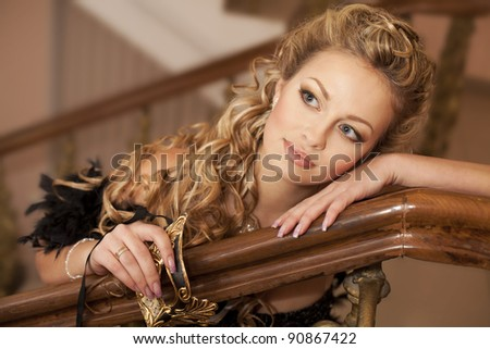 Fashion luxury retro portrait of beautiful sexy young woman with venice golden mask in the theater hall classic Interior art girl blond hair closeup  - stock photo