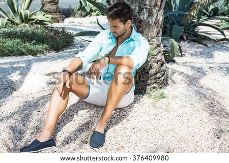 Fashion male model sitting under the palm tree and thinking - stock photo