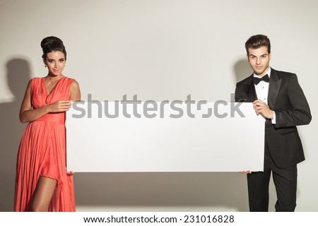 Fashion man and woman looking at the camera while holding a blank board. - stock photo