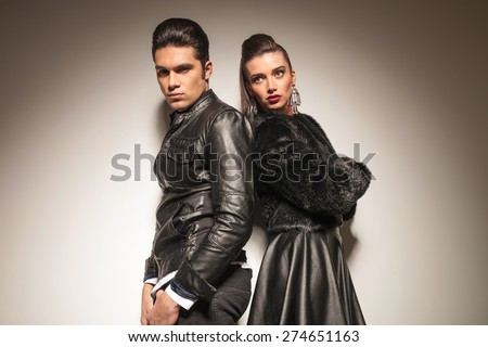 Fashion man and woman standing back to back on grey studio background.